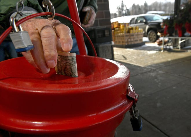 A shopper at the Giant Eagle store on Interchange Road in Millcreek Township puts cash in a Salvation Army kettle outside the store on Dec. 19, 2019.