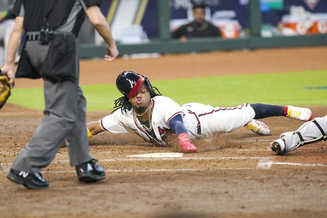 Atlanta Braves' Ronald Acuna Jr scores on a double by Marcell Ozuna during the third inning of Game 1 of a National League Division Series against the Miami Marlins Tuesday in Houston. [ERIC GAY / AP]