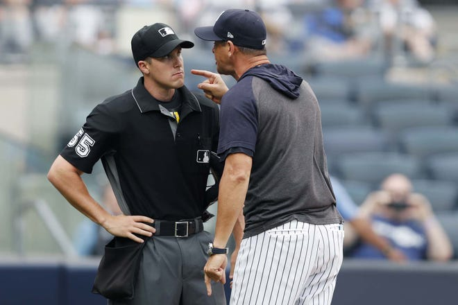 In this Thursday, July 18, 2019, file photo, New York Yankees' manager Aaron Boone yells at home plate umpire Brennan Miller during the first game of a \doubleheader against the Tampa Bay Rays in New York. The Rays and Yankees will play in the American League Division Series beginning Monday. [KATHY WILLENS / AP FILE]