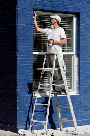 Rick Weikert puts the finishing touches on painting a window frame Oct. 6 in Burlington. He was finishing up his portion of working on the project that also included tuck pointing the building, priming it and painting.