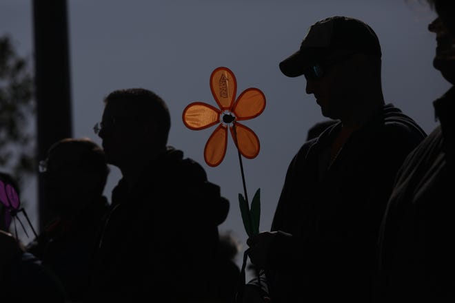Tim Wyckoff of Burlington holds a Promise Garden flower while listening to a speaker before the start of the 2019 Walk to End Alzheimer's Oct. 12, 2019, at the Port of Burlington.