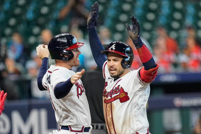 Atlanta Braves' Travis d'Arnaud, right, celebrates with teammate Freddie Freeman after hitting a three-run home run during the seventh inning in Game 1 of the National League Division Series against the Miami Marlins on Tuesday in Houston.