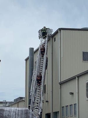 Firefighters scale up a ladder to extinguish a fire on Friday at a paper plant in Haines City.