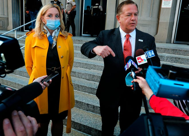 Mark McCloskey addresses the press alongside his wife Patricia on Tuesday outside the Carnahan Courthouse, in St. Louis, Mo.  A grand jury on Tuesday indicted the St. Louis couple who displayed guns while hundreds of racial injustice protesters marched on their private street.