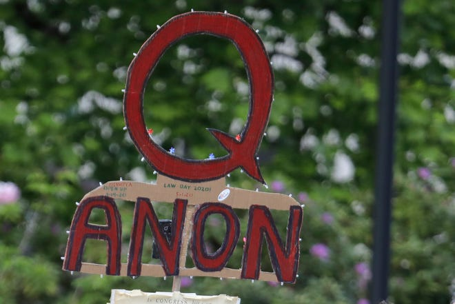 "A person carries a sign supporting QAnon at a protest rally in Olympia, Wash., in May. Facebook said Tuesday that it will remove Facebook pages, groups and Instagram accounts for ""representing QAnon."""
