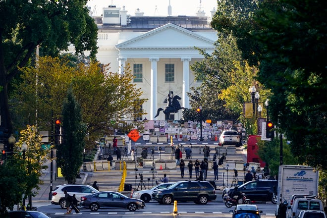 Traffic moves along K Street NW as TV crews set up in Black Lives Matter Plaza in front of  the White House early Tuesday.