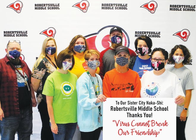 Robertsville Middle School staff members gathered to express thanks for the gift of more than 2,000 masks from friends in Oak Ridge's Sister City Naka-shi, Japan. Each one has traveled to Naka-shi as a chaperone for the exchange, representing years from the late 1990s through 2019. Front row: Michelle Brown, from left, Michelle Scott, Becky Childs, and Julie Lee. Back row: Sean Seyfert, Amy Randolph, Jaime Downs, John Quarles, Julie Kinder-McMillan, and Lauren Mayes.