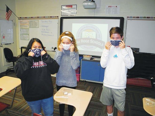 Robertsville Middle School students Monica White, from left, Elliott Norris, and Connor Rehill model masks from Oak Ridge's Sister City, Naka.
