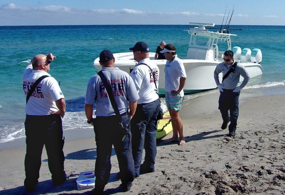 Palm Beach Fire Rescue crews stand along the shore with Danny Stanton (white visor and shorts) after his boat, Talley Girl, struck Carter Viss about 150 yards off shore on Nov. 28, 2019.