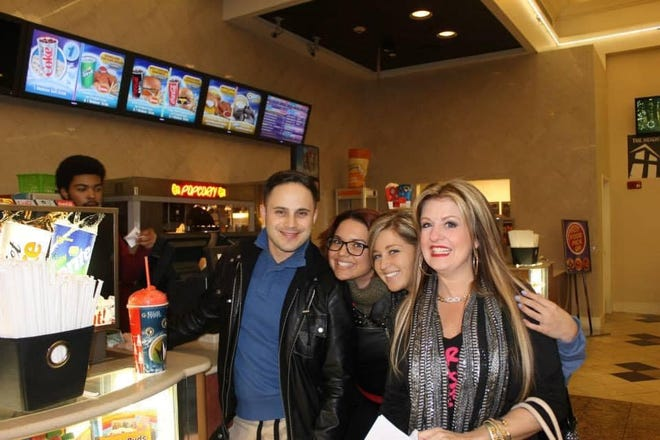 """From right to left, Alicia Amsler of Chesterfield, Alicia's friends Kasey, Sydney, and Jackson Scott of Richmond purchase snacks before viewing """"50 Shades of Grey"""" together at Regal Commonwealth & IMAX on February 12, 2015 in Chesterfield County."""