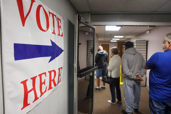 Voters spaced 6 feet apart wait their turn in line at the Portage County Board of Elections offices to cast their ballots Tuesday on the first day of in-person voting.