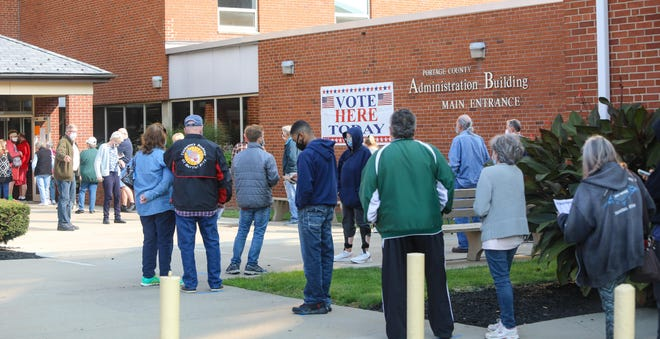 A line of voters winds up and down sidewalks on Tuesday morning outside the Portage County Board of Elections offices on the first day of in-person voting in Ohio.