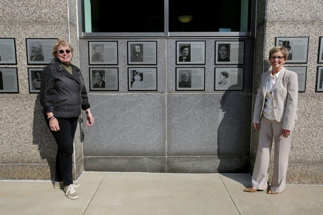 Local historian Margy Vogt (left) and City Safety Service Director Barbara Sylvester pose by the 45 historical Massillon plaques that have been updated and relocated from Diamond Court to City Hall Street SE.
