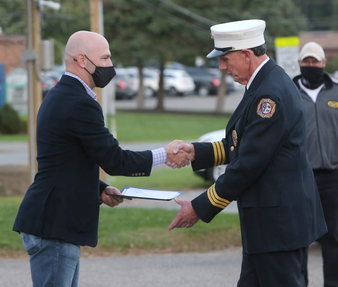U.S. Rep. Anthony Gonzalez (left) recognizes Harry Ellis for his 39 years of service during a ceremony honoring Perry Township firefighters in October at the Perry Township Administration Office.