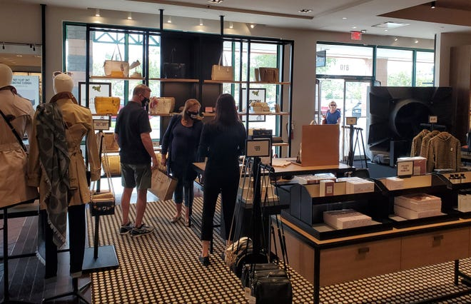 Shoppers visit the Michael Kors outlet store in St. Augustine on Friday. The company's policy has been to continue to limit the number of customers in stores at one time. [COLLEEN MICHELE JONES/THE RECORD]