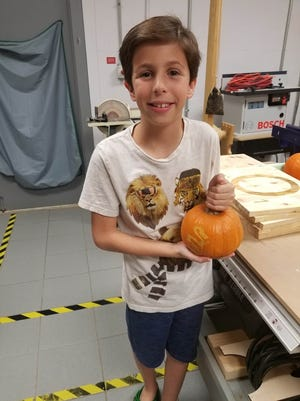 A Fab Lab participant holds his custom laser-etched pumpkin.