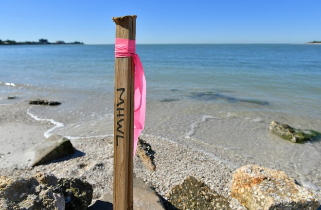 Stakes mark the mean high water line, which separates public beach from a homeowner's private property, at Shell Beach on Siesta Key.