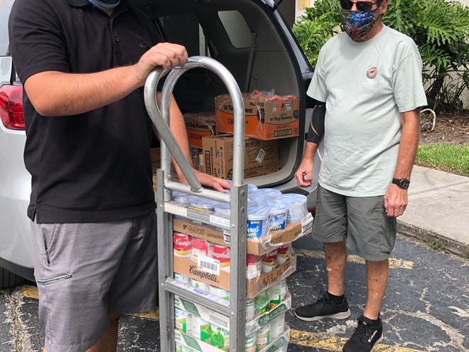 Temple Beth Sholom facilities manager Duane Rushing with Sid Finkelstein, who donated cases of canned food.