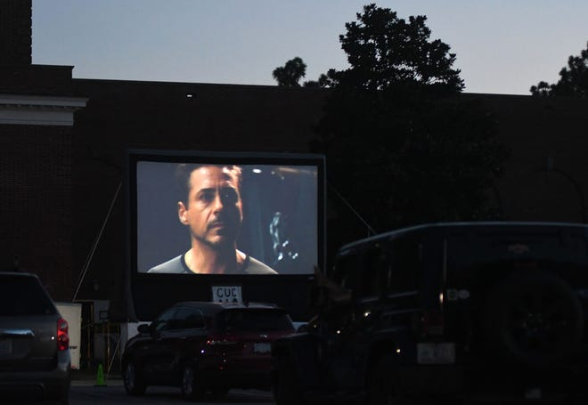 "People watch ""Iron Man 3"" from their cars during the first night of Curbside Cinema at UNCW in Wilmington, N.C., on July 10."