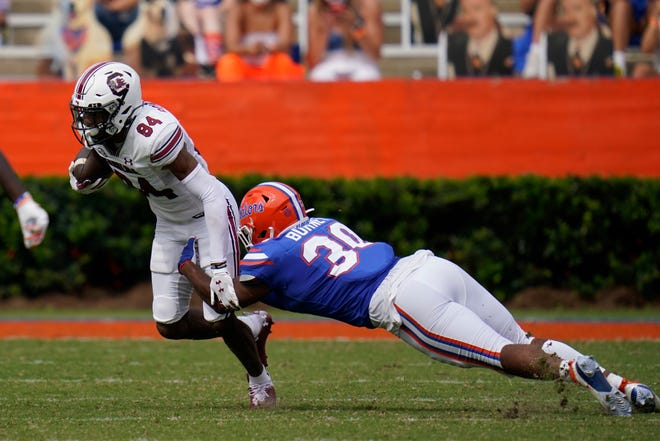 South Carolina wide receiver Rico Powers Jr. is stopped by Florida linebacker Amari Burney after a reception during the second half Saturday at Ben Hill Griffin Stadium.