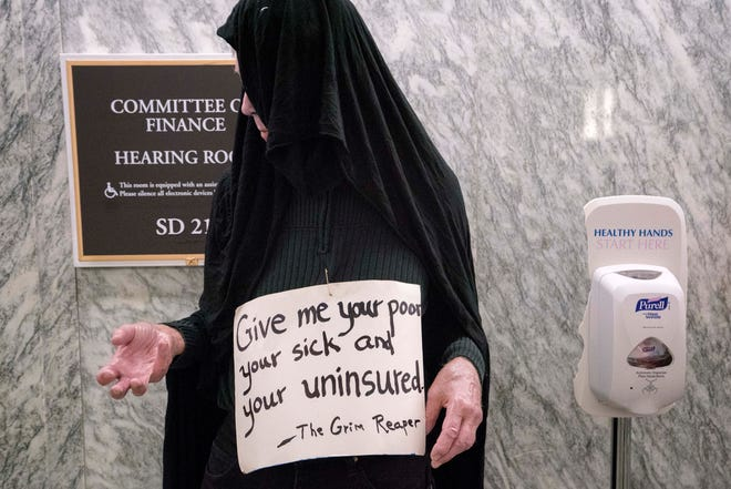 A man dressed as the Grim Reaper protests outside a Senate hearing room where health care proposal was being considered in 2017.