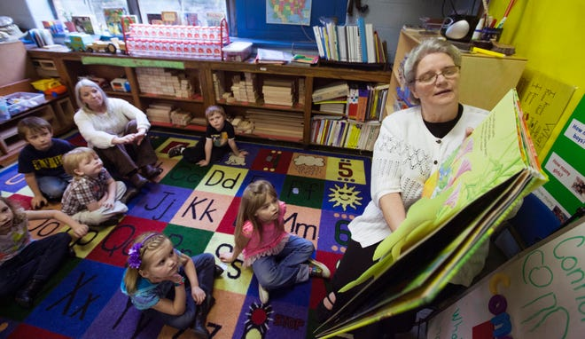 An early childhood teacher reads to pre-K students in 2013.