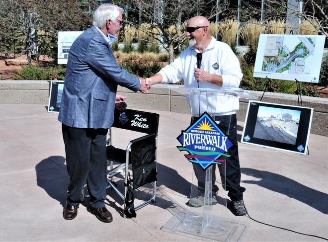 For his two decades of service to the Historic Arkansas Riverwalk of Pueblo Authority board, Ken White, left, receives a commemorative chair and handshake from fellow board member Dave Anderson.