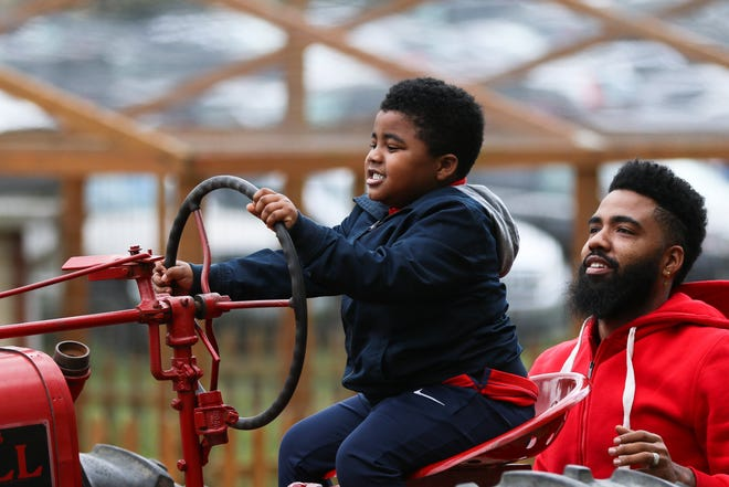 Terry Arter of Columbus watches as his son Xavier Arter, 3, pretends to drive a tractor during a trip to Pigeon Roost Farm in Hebron on Oct. 3.