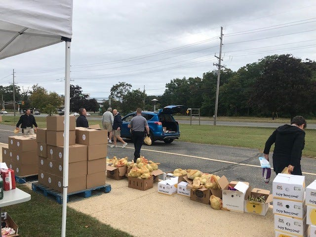 Volunteers fill trunks with free food at the Toms River food distribution site at the Presbyterian Church of Toms River, Oct. 2 2020.
