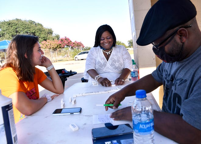 Sheria Davis (center) plays dominoes with Patterson Newton (left) and Jeromy Ray at Stevenson Park on Oct. 3. Davis is a candidate for Abilene City Council.