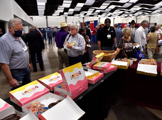 Attendees at the 98th annual County Judges and Commissioners Association of Texas Conference help themselves to snacks during a break Tuesday at the Abilene Convention Center.