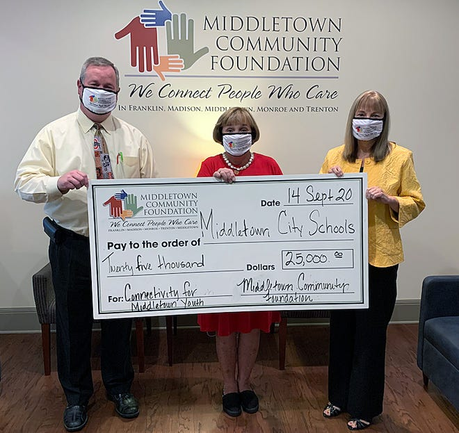 The Middletown Community Foundation presented the Middletown City Schools with a $25,000 check to kick off its Connect Middletown Youth initiative to defer the cost of Wi-Fi hotspots. From left are treasurer Randy Bertram, foundation president Patti Gage, and foundation CEO Traci Barnett.