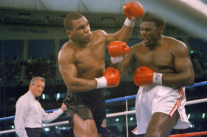Challenger Tony Tubbs grimaces as champion Mike Tyson lands a head shot in the 2nd round of scheduled 12 round title bout at the Tokyo Dome indoor baseball stadium, Monday, March 21, 1988. Tyson defended his undisputed heavyweight crown with a 2nd round knockout.