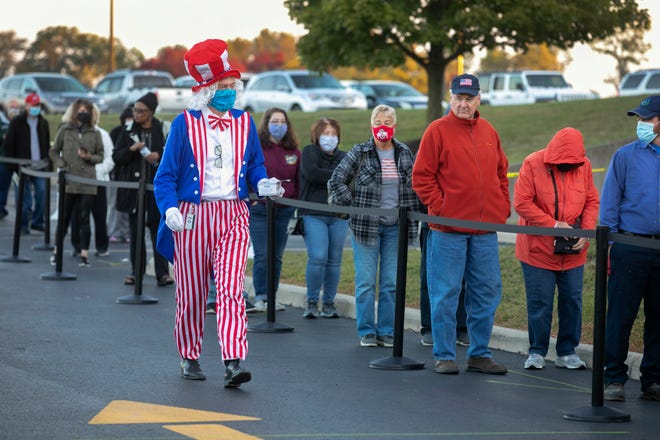 Rick Smith, precinct executive for the Warren County Board of Elections in Lebanon, manages the line, Tuesday, Oct. 6, 2020. Oct. 6 was the first day of early voting in Ohio. Masks are required. Smith was offering masks if someone forgot. Voting numbers are expected to be up this year because of the presidential election between President Trump and former Vice President Joe Biden