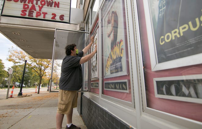 Historic Howell Theater owner Tyler DePerro prepares to post new release movie posters in front of his downtown theater Tuesday, Oct. 6, 2020.