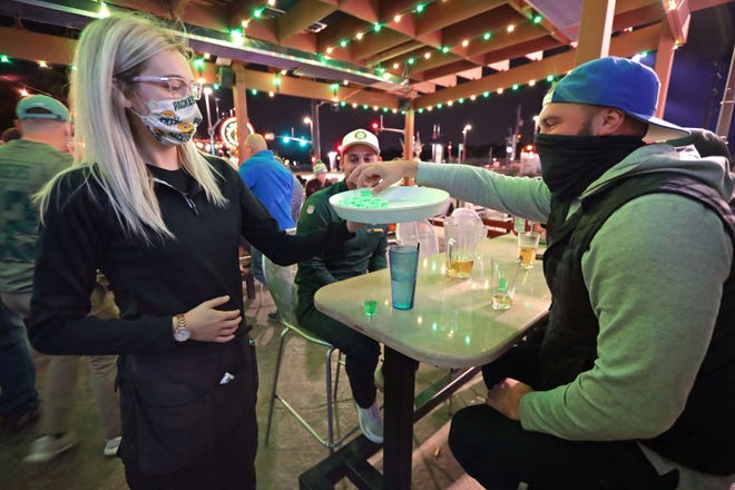 Steve Drinka, right, of Milwaukee, gets a free touchdown shot from server Hanna Marks after the Green Bay Packers scored a touchdown against the Atlanta Falcons. He was watching the game at Leff's Lucky Town on West State Street in Wauwatosa on Monday. Crowds at area bars varied as people gathered to watch the Packers game despite the coronavirus risk.
