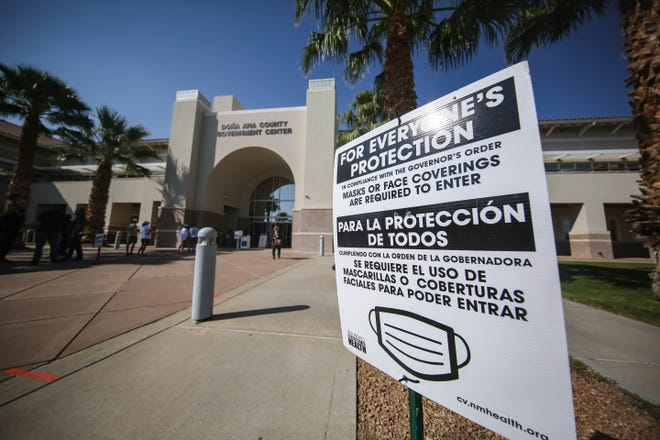 A sign instructs voters on COVID-safe practices at the Doña Ana County Government Center in Las Cruces on the first day of early voting, Tuesday, Oct. 6, 2020.
