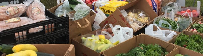 Fresh produce and packaged goods donated by Farmington Farmers Market farmers and vendors wait to be loaded into a truck bound for the food pantry at C.A.R.E.S. of Farmington Hills last Saturday.
