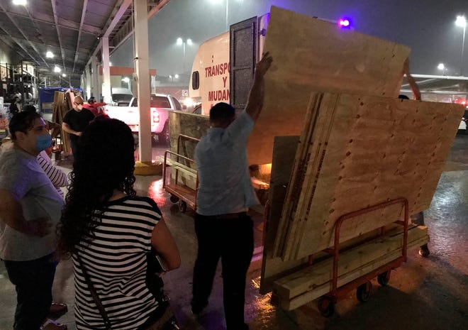 Personas acuden a tiendas para adquirir víveres o maderas, en el balneario de Cancún, estado de Quintana Roo (México).