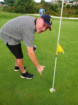 Jon Strathmeyer points to the ball in the hole after his most-recent hole-in-one at Bridgewater Golf Club.