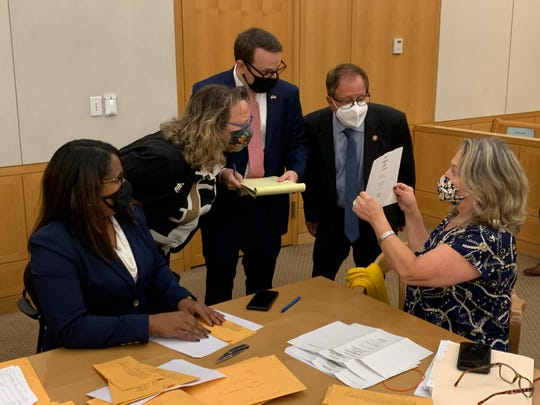 Members of the Westchester County Board of Elections in New York open ballots contested in the Tuckahoe Village Board elections and show them to attorneys for the Democratic and Republican candidates on Oct. 5, 2020.