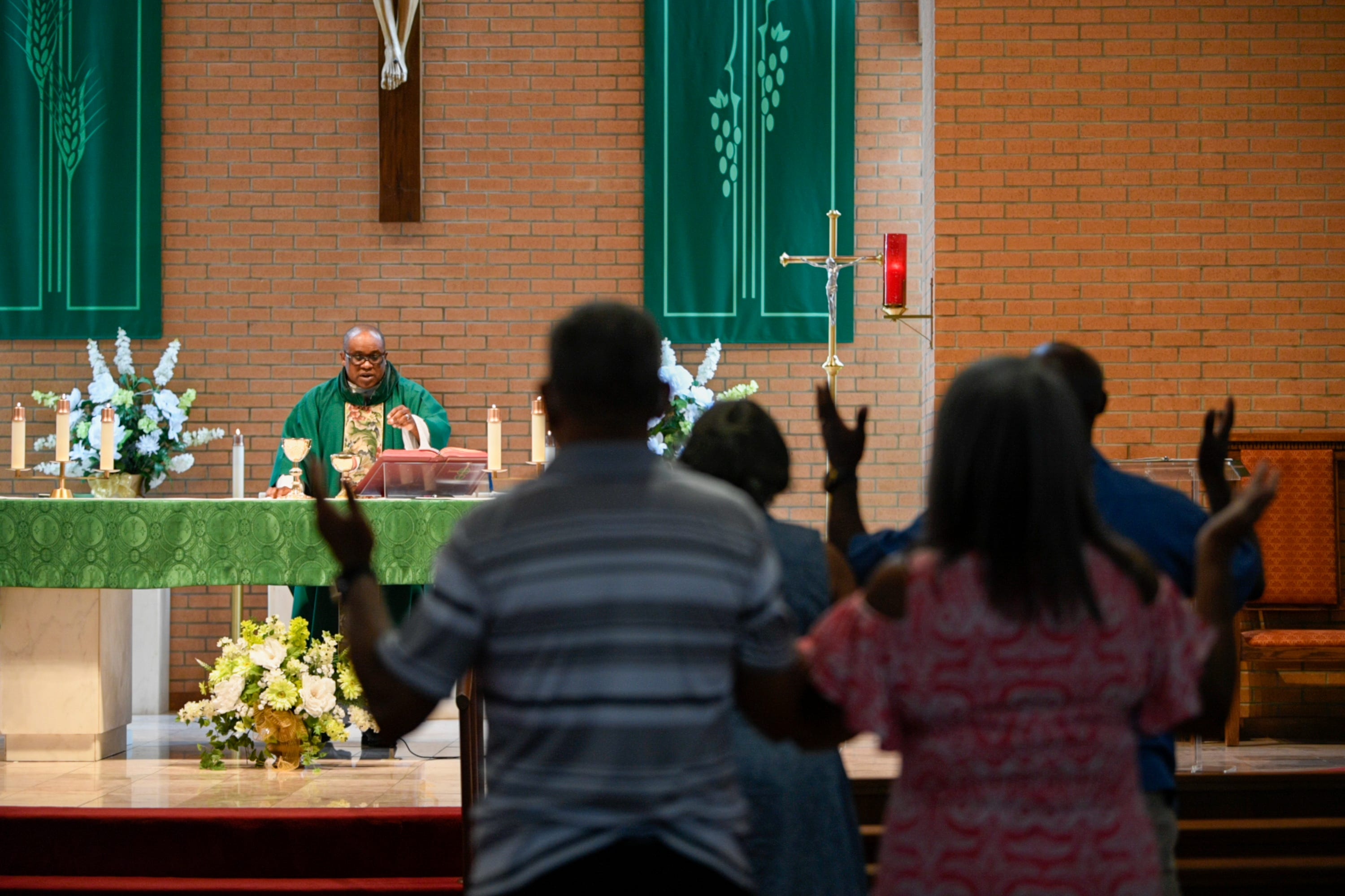 Parishioners stand in Our Lady of Grace Catholic Church in Reserve, La., during a sermon by the Rev. Christopher Chike Amadi.