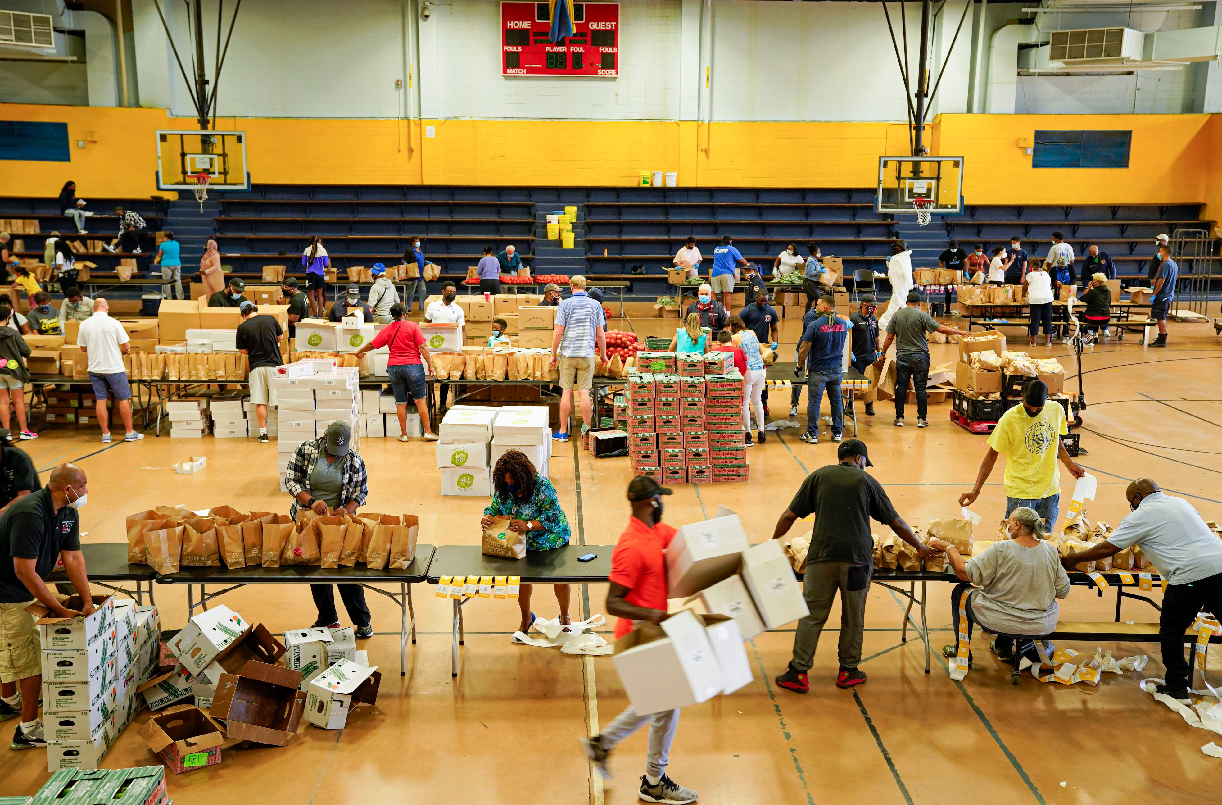 Volunteers, mostly city employees, help pack bags of food for families in need at the John F. Kennedy Recreation Center in Newark.