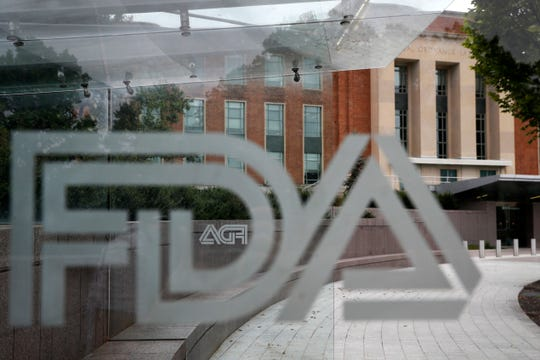 This Aug. 2, 2018, file photo shows the U.S. Food and Drug Administration building behind FDA logos at a bus stop on the agency's campus in Silver Spring, Md.