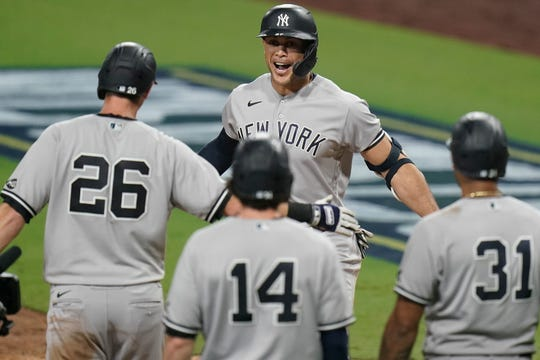 Giancarlo Stanton, center, celebrates with teammates after hitting a grand slam home run in the ninth inning.
