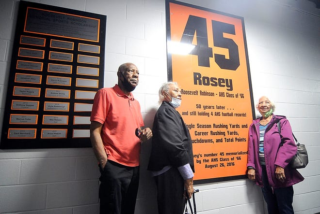Roosevelt Robinson's brother James L. Robinson and sisters Earlene Harris and Mary Smith pose for a photo with the plaques in Rosey's Memorial Hall in the Keith Wygant Memorial Field House on Wednesday.
