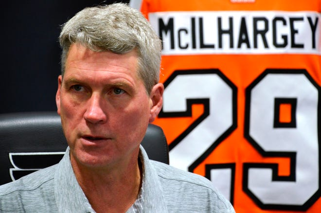 GM Chuck Fletcher prepares to make the Flyers' first-round pick Tuesday night with the jersey of Jack McIlhargey, a former Flyers defenseman, assistant coach and scout who died of cancer on July 19.