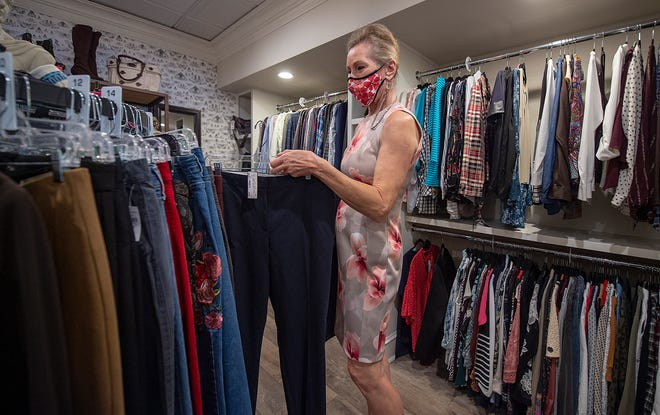 Debbie Haines, owner of Dress to the 9's shop in Newtown, stocks the racks with new consigned merchandise on Tuesday.