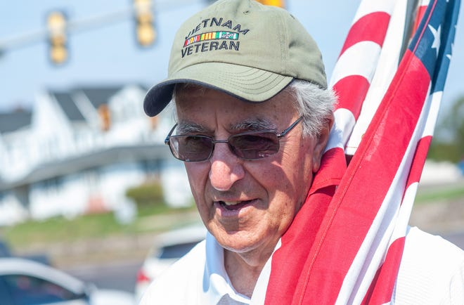 Jerry Sisian holds an American flag while sitting outside waving at people showing his support for America and for Law Enforcement on Wednesday in Upper Southampton.