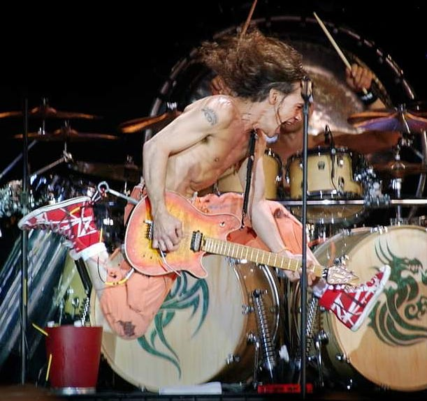 Eddie Van Halen, shown in mid-jump during a 2004 concert at Star Lake Amphitheatre in Burgettstown, died Tuesday of mouth cancer. He was 65. [Jason L. Neslon]